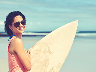 woman wearing sunglasses carrying a surfboard